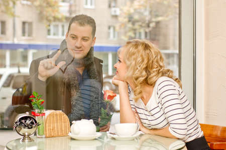 Date  Attractive young blond woman and her boyfriend at small cafe  Guy with rose draws a heart on the glass Stock Photo - 16932718