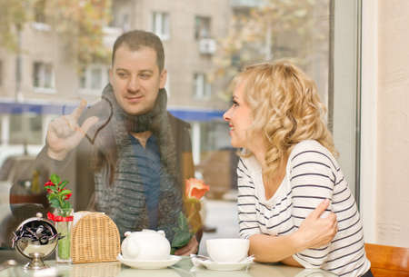 Date  Attractive young blond woman and her boyfriend at small cafe  Guy with rose draws a heart on the glass  Stock Photo - 16932708