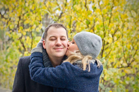 Date  Young woman kisses a smiling man  Autumn
