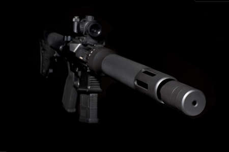 silencer: Assault semi-automatic rifle with short silencer on dark background. Isometric view. Short   depth of field.