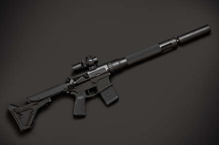 the silencer: Assault semi-automatic rifle with silencer on dark grey background. Right side.