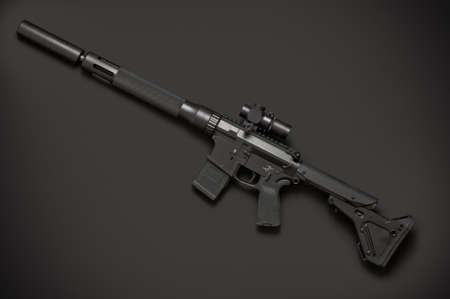 the silencer: Assault semi-automatic rifle with silencer on dark grey background. Left side. Stock Photo