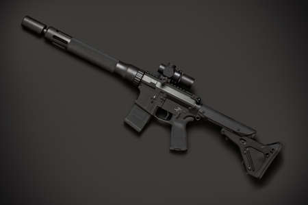 the silencer: Assault semi-automatic rifle with short silencer on dark background. Left side.
