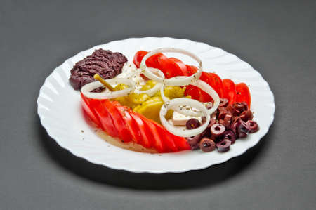 White ceramic plate with marinated olives, tomatoes, pepper, onion, feta cheese, olive oil and spice mix on grey background