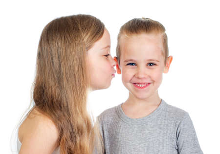 Young smiling caucasian boy and girl kisses him on the cheek isolated on white background Foto de archivo