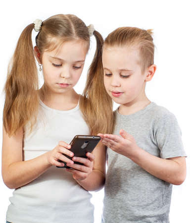 Young caucasian boy and girl with mobile phone isolated on white background
