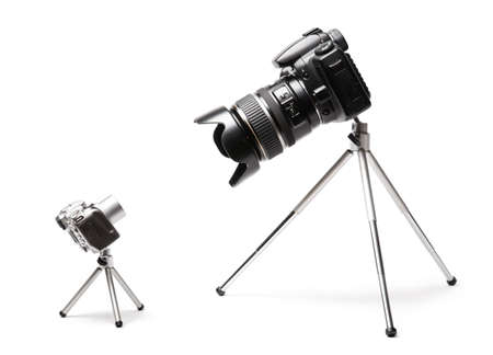 superiority: Two cameras big and small. Isolated on white. Stock Photo