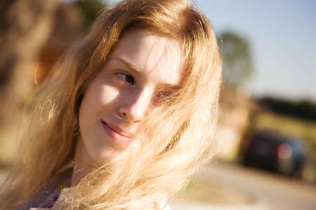 Young woman with fluttering hair outdoors. Focus on hair. photo