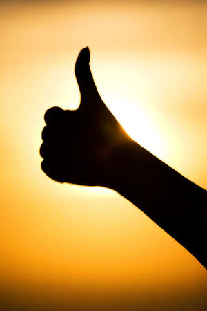 Excellent hand sign silhouette. On bright sun background.
