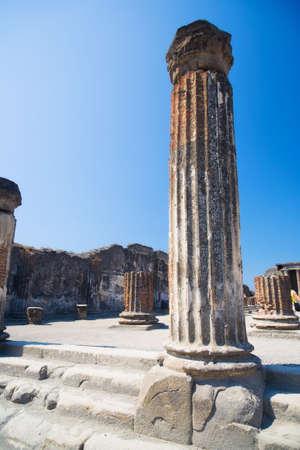 pompeii: Antique column on blue sky background. Pompeii Italy.