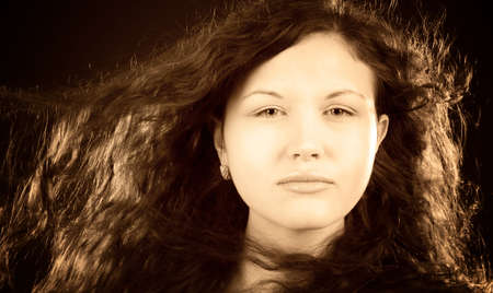 Young seious woman with fluttering hair. Retro sepia colors. Stock Photo - 5061230