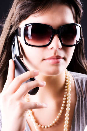 Young woman with mobile phone. On dark background. Stock Photo - 5061225