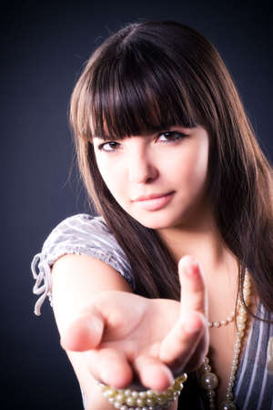 Young woman stretching hand. On dark background. Stock Photo - 5061223