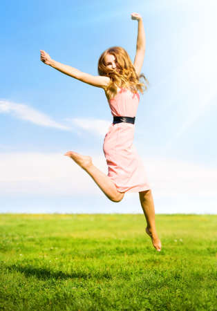 Happy jumping girl on summer field background. photo