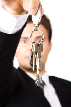 Young businessman holding keys. On white. Stock Photo - 5088976