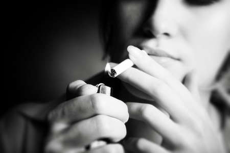 Smoking woman. Focus on cigarette lighter. photo