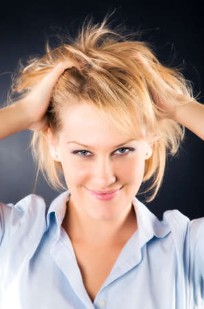 Cheerful woman with dishevelled hair. On dark background. Stock Photo - 5104366