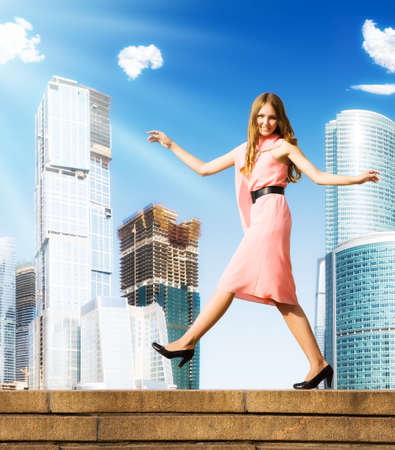 Young careless woman walking on skyscrapers background. photo