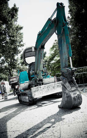 Excavator in a city. Dramatic colors and angle of view. photo
