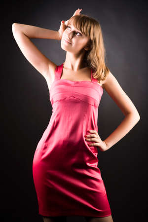 Young slim woman in pink dress. On dark background. Stock Photo - 5142596