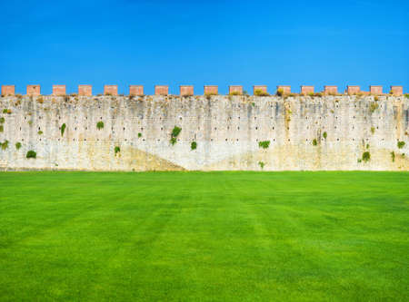 Ancient wall blue sky and green grass. photo
