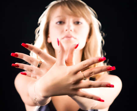 Young woman showing her red nails. On dark background. Stock Photo - 5159288