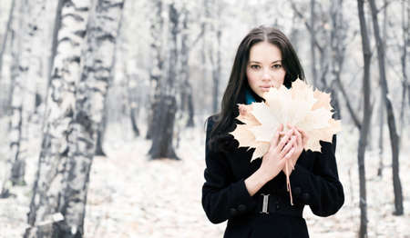 Brunette woman with maple leaves. Bright white autumn forest background. photo