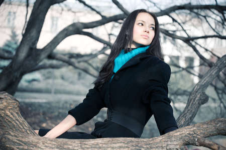 Young woman on a branch. Autumn season. photo
