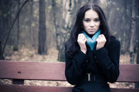Young woman sitting on a bench. Autumn season. photo