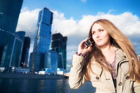 Young businesswoman with mobile phone. On modern city background. Stock Photo - 5179161