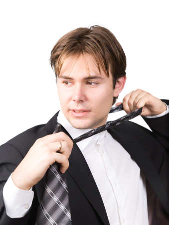 Tired businessman taking off his tie. Isolated on white. photo