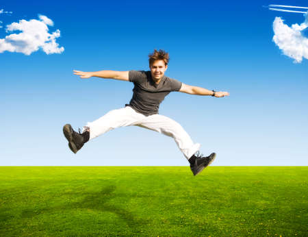 Happy jumping man on summer landscape background. photo