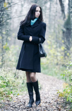 Slim brunette woman walking in a park. Autumn season. photo