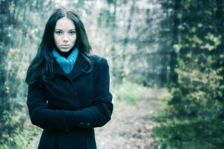 myst: Young woman outdoors portrait. Grungy background with for aged photo effect.