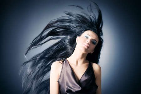 Woman with fluttering hair. On dark background. photo