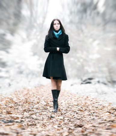 lonesome: Slim brunette woman walking in a park. Special background blur effect. Stock Photo
