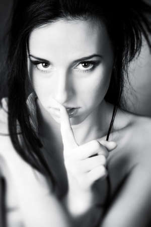myst: Young woman showing quiet sign. Black and white concept portrait.