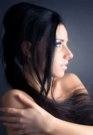 Young brunette woman profile portrait. On dark background. photo