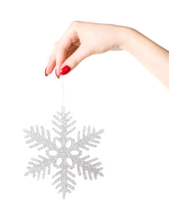 Woman hand holding big holiday snowflake. Isolated on white. photo