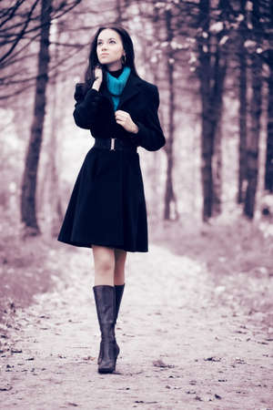 Young woman walking in forest. Soft pink and blue tint. photo