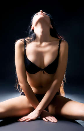 Sexy delighting woman in lingerie. On dark background. photo