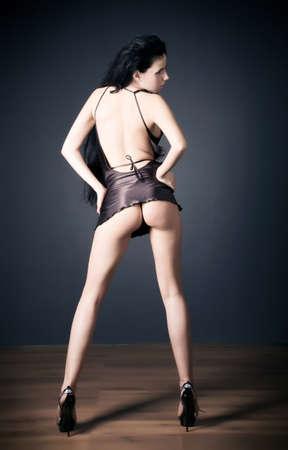 y slim woman in short dress. Backside view. photo