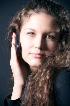 Young woman with mobile phone. On dark background. Stock Photo - 5217089