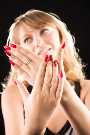 Young woman showing her red nails. On dark background. photo