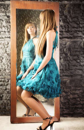 Coquet woman in front of the mirror. On stone wall background. photo