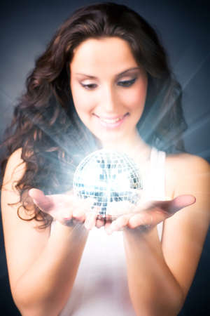 Young woman with magic shine ball. On dark background. Stock Photo - 5242663