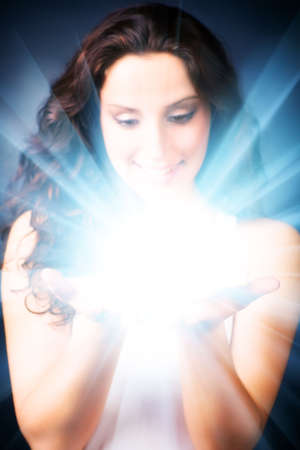 black magic: Young woman with magic shine in hands. On dark background.