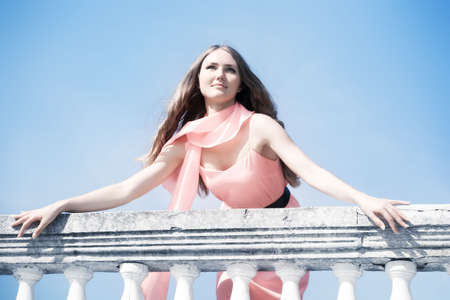 Young romantic woman standing at the railing. photo