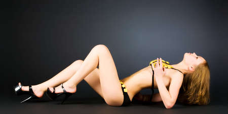 Sexy slim woman in lingerie. On dark background. photo