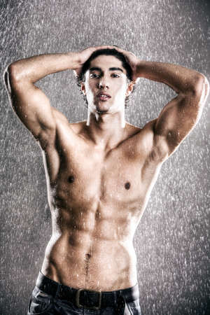 Young muscular man under the rain. High contrast effect. photo